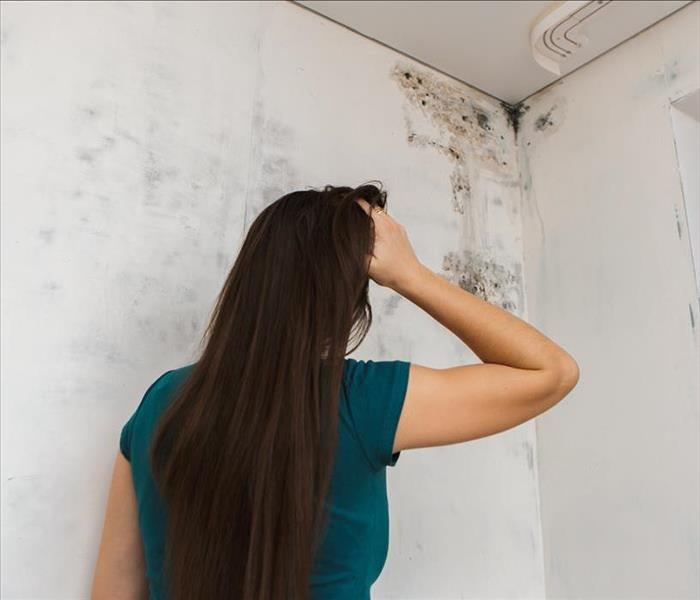 Woman holding her head while watching mold on the corner of the roof of the house