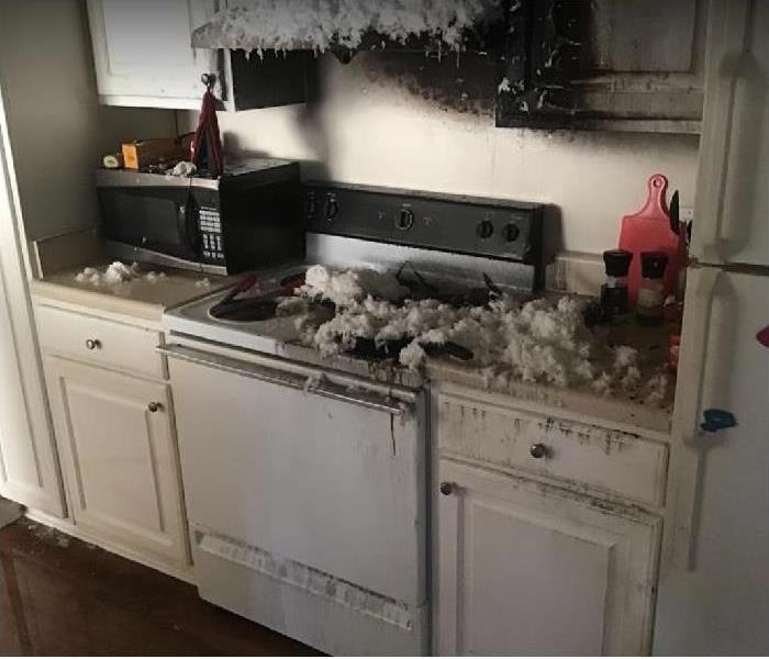 Fire damaged kitchen. Fire suppression residue on stove and counter; soot and some residue on walls.